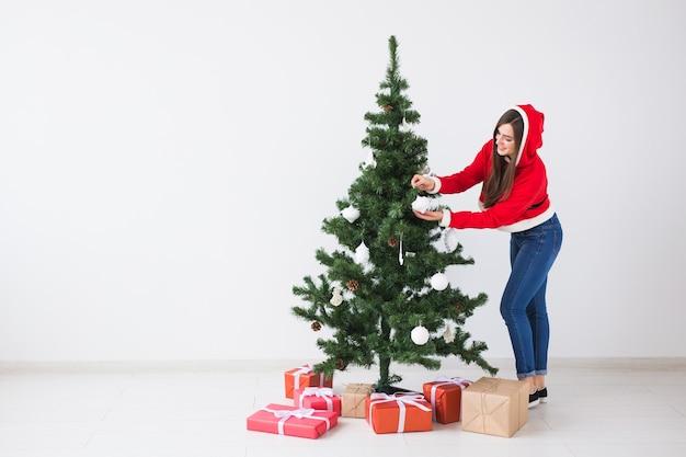 Wintervakantie xmas en mensen concept gelukkige jonge vrouw gekleed in santa kostuum decoreren