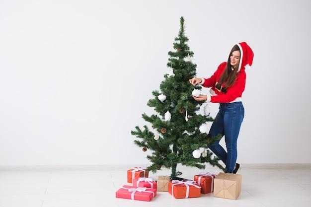 Wintervakantie xmas en mensen concept portret van mooie jonge vrouw in kerstmuts versieren