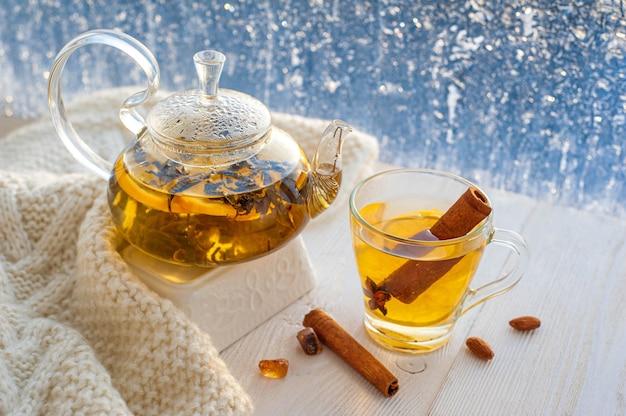 Winterverwarmende thee met citroen en sinaasappel tegen de achtergrond van ijzige patronen.
