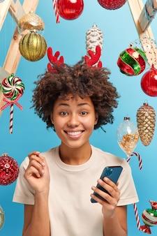 Winterviering en feestelijk evenementconcept. glimlachende blij donkere vrouw ontvangt groet sms op smartphone tijdens oudejaarsavond draagt rendieren hoepel bereidt zich voor op wintervakantie. gezellige sfeer