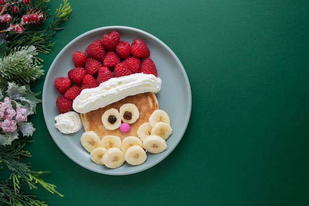 Wintervoedsel voor kinderen. de kerstmanpannekoek van kerstmis met framboos en banaan voor kindermenu.