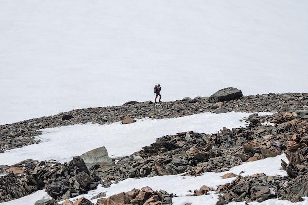 Winterwandelen in de met sneeuw bedekte bergen. hooglandlandschap met geslepen stenen van ongewone vorm. geweldig schilderachtig berglandschap met grote gebarsten puntige stenen onder sneeuw in zonlicht.