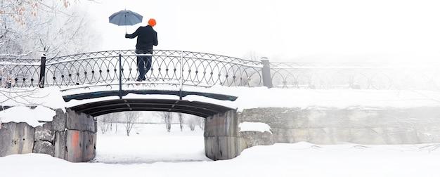 Winterwandeling met een paraplu. man in een jas met een paraplu, lopen tegen de achtergrond van het winterlandschap, winterzicht