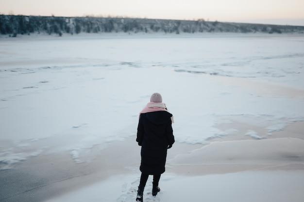 Winterwandeling. vrouw die op bevroren rivierachtergrond in koude tijd loopt.