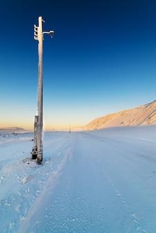 Winterweg in de bergen. inactieve lichtmast.