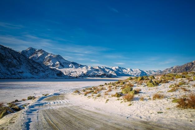 Winterweg in de bergen. rocky mountains zijn bedekt met sneeuw tegen de blauwe lucht in zonlicht. roadtrips naar wilde oorden.