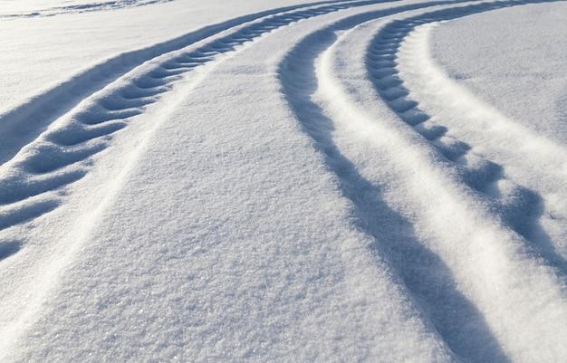Winterweg met sporen van auto's in het winterseizoen, bedekt met sneeuw na sneeuwval