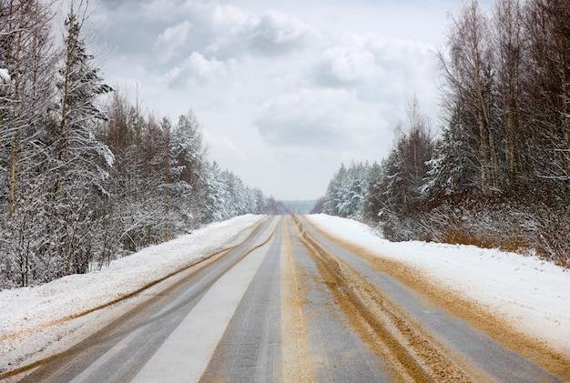 Winterweg verdwijnt in de horizon en verandert in anti-glazuursamenstelling