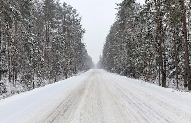 Winterweg voor autorijden in de winter, bedekt met sneeuw na sneeuwval Premium Foto