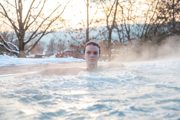 Winterzwembad met een jonge ontspannende vrouw.