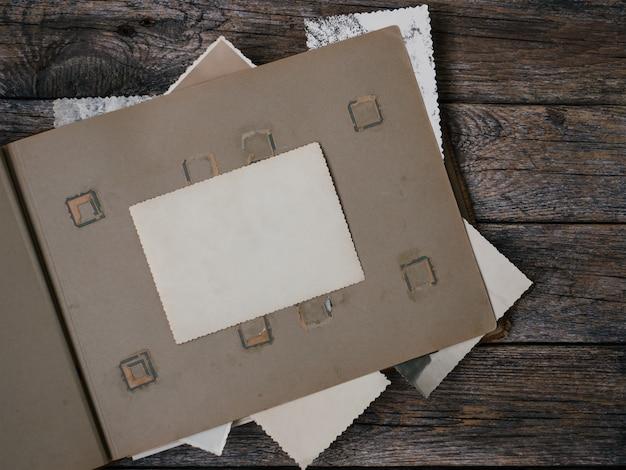 Wis lege fotolijsten om uw foto's of tekst op een oud familiealbum op een houten bordachtergrond in retrostijl te plaatsen