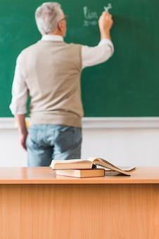 Wiskundeleraar die op bord dichtbij lijst met boeken schrijven