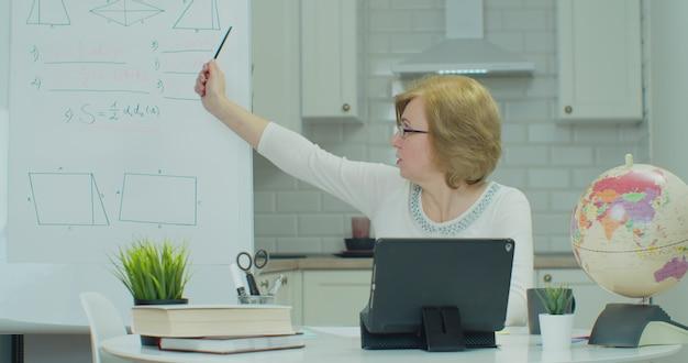 Wiskundeleraar in brillen videochatten met studenten