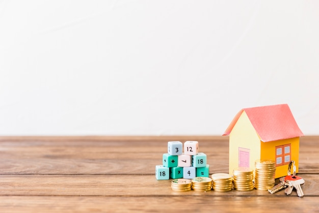 Wiskundige blokken, huis, sleutel en gestapelde munten op houten oppervlak