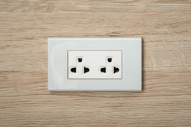 Wisselstroomstekkers en stopcontacten in houten muur.