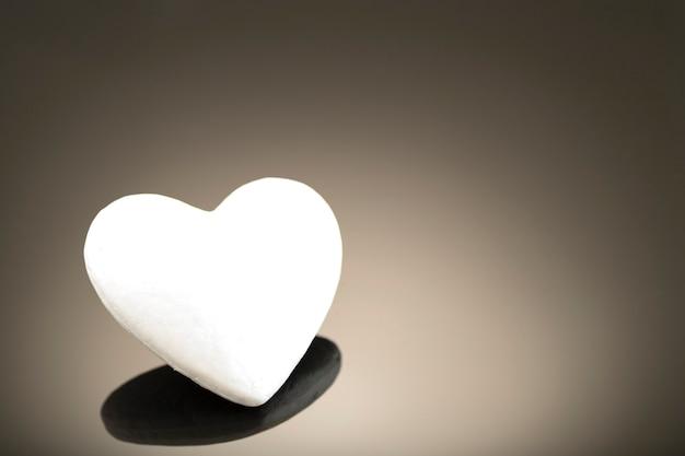 Wit 3d hart gemaakt van polystyreen, op een donkere ondergrond met plaats voor tekst