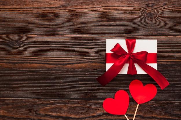 Wit aanwezig met een rood lint en papieren harten geïsoleerd op een donkere houten achtergrond. bovenaanzicht van een feestende warme flatlay. valentijnsdag en kerst concept. copyspace.