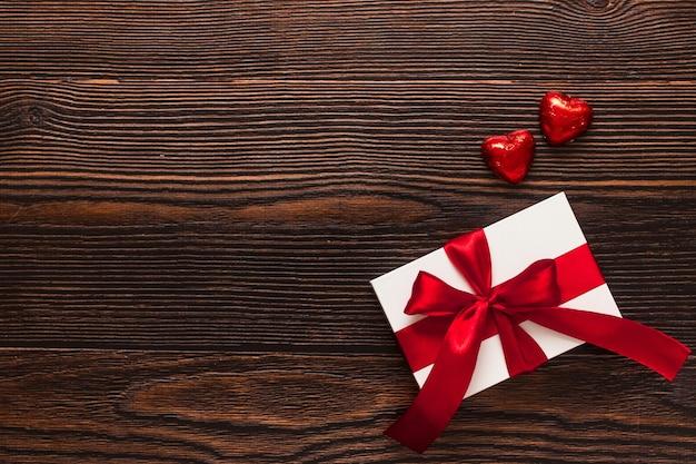 Wit aanwezig met een rood lint en twee chocolade rode harten geïsoleerd op een donkere houten achtergrond. bovenaanzicht van een feestende warme flatlay. valentijnsdag en kerst concept. copyspace.