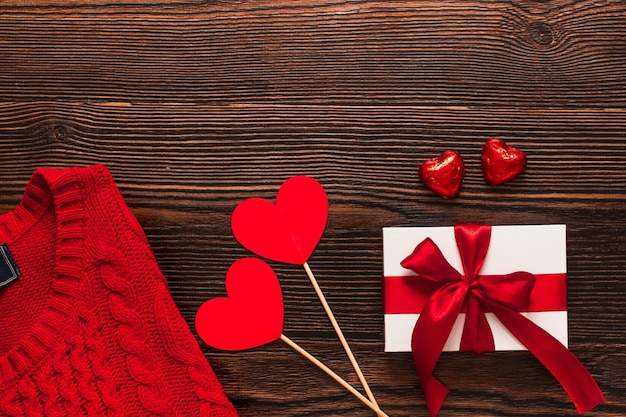 Wit aanwezig met een rood lint, rode trui, papieren hartjes op stokjes en twee chocolade rode harten geïsoleerd op een donkere houten achtergrond. bovenaanzicht van flatlay. valentijnsdag concept. copyspace.