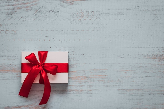 Wit aanwezig met rood lint op een licht geschilderde houten achtergrond. bovenaanzicht, plat liggend. valentijnsdag concept. copyspace.