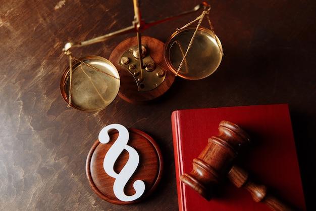 Wit alineasymbool en houten rechterhamer in rechtszaalrecht en rechtvaardigheidsconcept