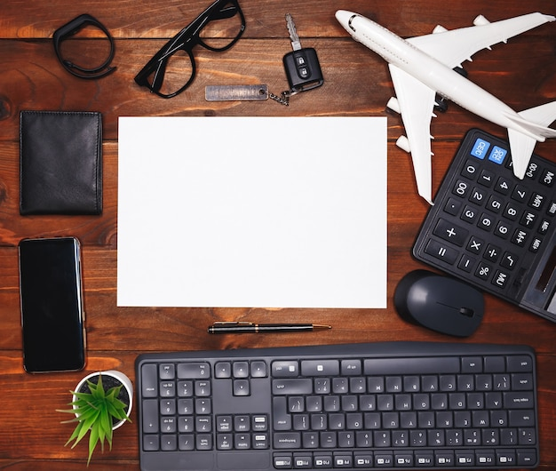 Wit blad op donkere houten bureautafel met veel benodigdheden. bovenaanzicht, plat gelegd. moderne bureaudesktop met toetsenbord, muis en kleine groene installatie. zakelijke achtergrond met computeraccessoires