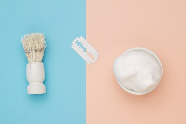 Wit blad, schuim en scheerkwast op beige en blauwe achtergrond.