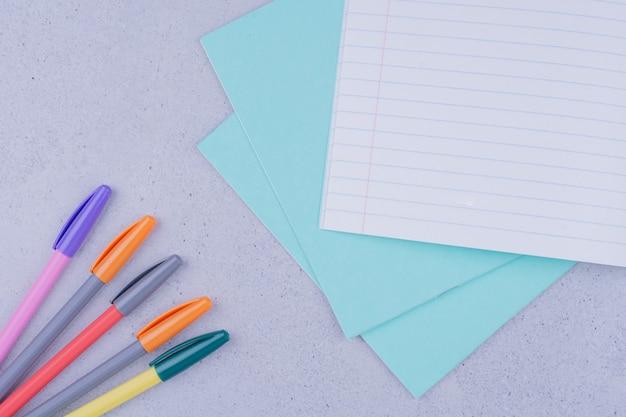 Wit blanco gecontroleerd papier met pen op grijs oppervlak