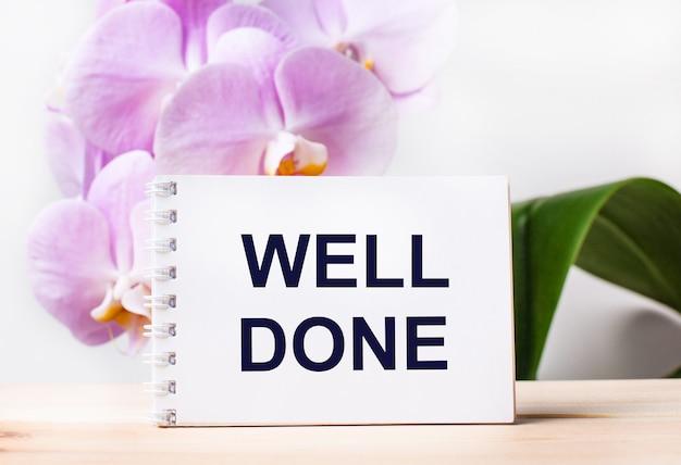 Wit blanco notitieboekje met de tekst well done op tafel tegen de achtergrond van een lichtroze orchidee.