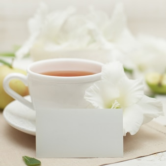 Wit blanco papier, gladiolen bloem en kopje thee