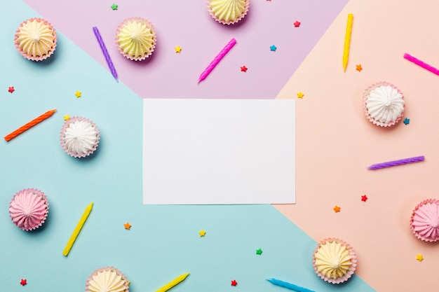 Wit blanco papier omringd met kaarsen; hagelslag; aalaw op gekleurde achtergrond