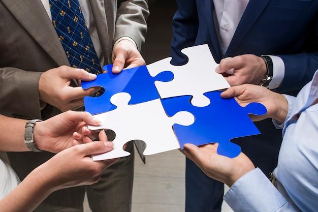 Wit-blauwe puzzel in de handen van professionals