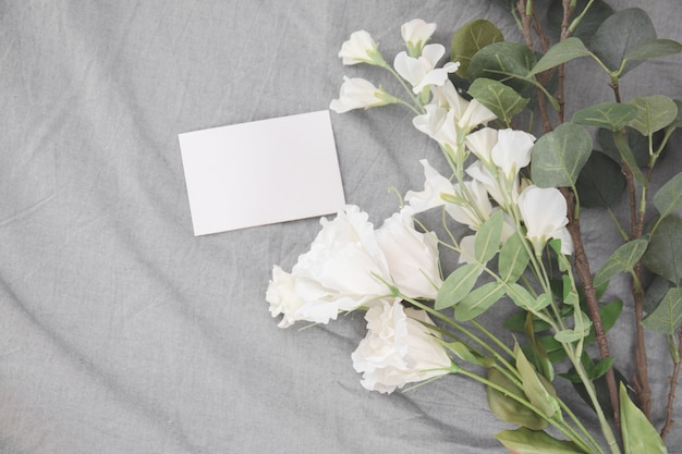 Wit bloemen romantisch boeket en de lege stapel van de beeldverhaalkaart op bed.