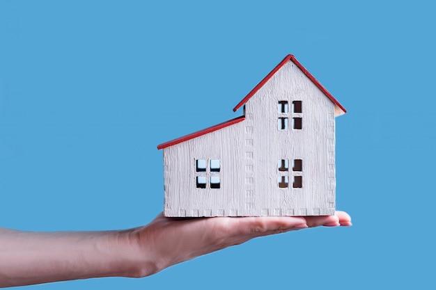 Wit blokhuis op een vrouwelijke hand. blauwe achtergrond. huisvestingsconcept