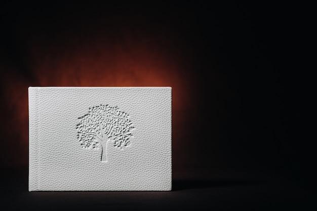 Wit boek van echt wit leer op een donkere achtergrond met reliëf. witboek op een donkere achtergrond.
