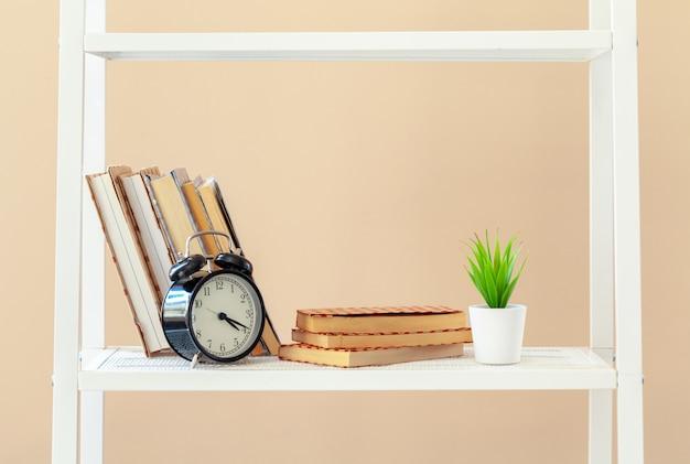 Wit boekenrek met boeken en kantoorbehoeften tegen beige muur