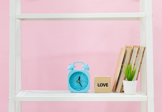 Wit boekenrek met boeken en plant tegen roze muur
