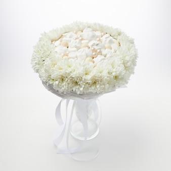 Wit boeket van marshmallows en chocolade omlijst door witte bloemen staat in een vaas op wit