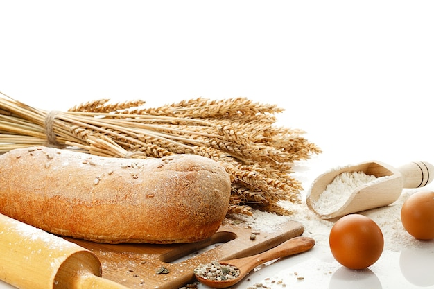 Wit brood en kookgerei geïsoleerd op een witte tafel