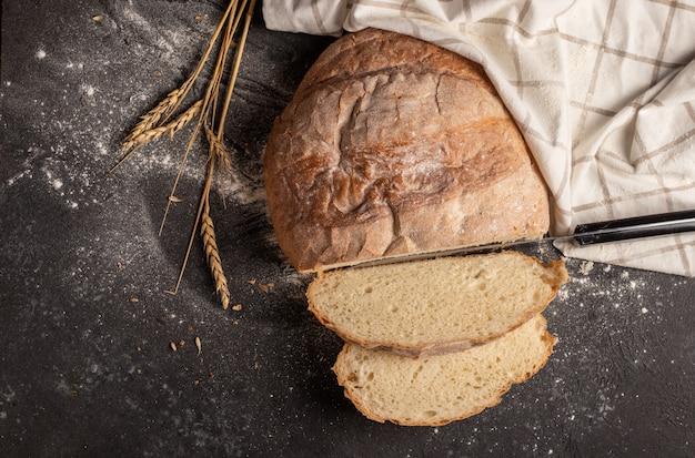 Wit brood in stukjes gesneden met een wit geruit servet en aartjes tarwe op zwart