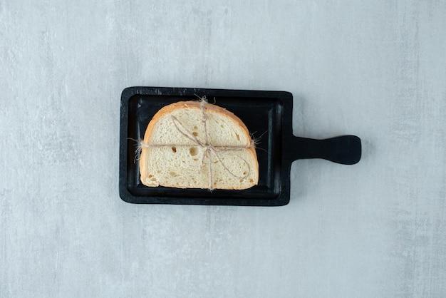 Wit brood vastgebonden met touw op een donkere bord.
