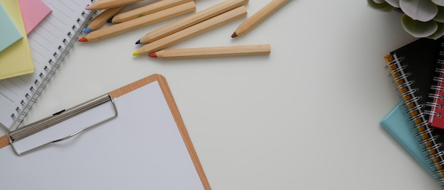 Wit bureau met papier op klembord, briefpapier, andere kantoorbenodigdheden en kopie ruimte