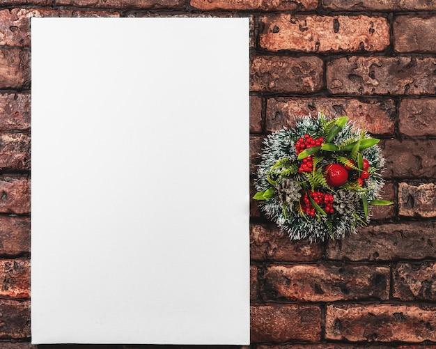 Wit canvas en een kroon van kerstmis op een achtergrond van rode bakstenen muur