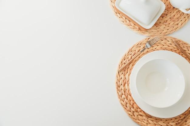 Wit ceramisch vaatwerk, vezel gevlecht rond placemat en bestek dat op witte achtergrond wordt geplaatst. scandinavische stijl.