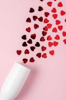 Wit champagneglas met scheutje rode hartvormige confetti over roze oppervlak.