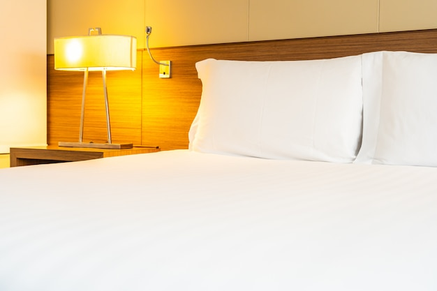 Wit comfortabel kussen en deken op bed met lichte lamp