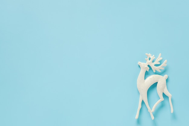 Wit de hertenstuk speelgoed van de kerstmisdecoratie op blauwe achtergrond met exemplaarruimte