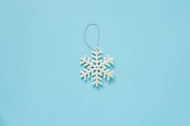 Wit de sneeuwvlokstuk speelgoed van de kerstmisdecoratie op blauwe achtergrond met exemplaarruimte