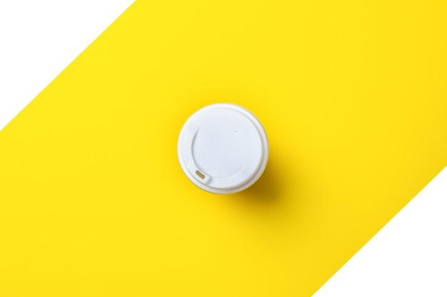 Wit deksel op een kartonnen glas van bovenaf op een geel-wit.