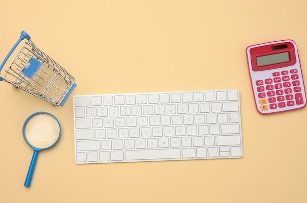 Wit draadloos toetsenbord en leeg winkelwagentje, vergrootglas op beige achtergrond, budgetanalyseconcept, besparingen. online winkelen
